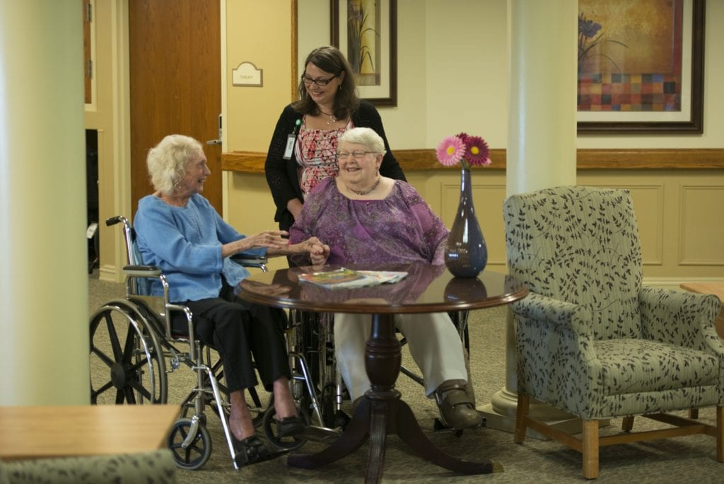 Residents and nurse talking at United Zion retirement